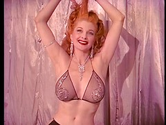 Vintage redheaded burlesque babe with her sexy big tits in a lingerie top
